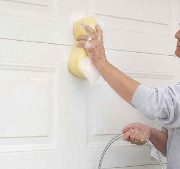 Limpiando una puerta de garaje con esponja y jabón